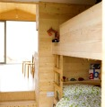 Designer Nina Tolstrup's tiny beach hut comfortably accommodates her family of four in its 388 sq ft. | www.facebook.com/SmallHouseBliss
