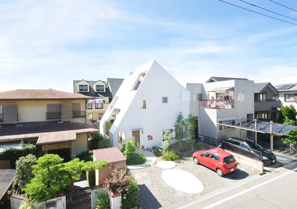 This small house for a family features terraces cut into the steeply pitched roof.   www.facebook.com/SmallHouseBliss