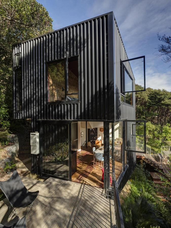 This vertically-oriented house with 1 bedroom and a small loft in 872 sq ft uses a split-level design to step down its steep site. | www.facebook.com/SmallHouseBliss