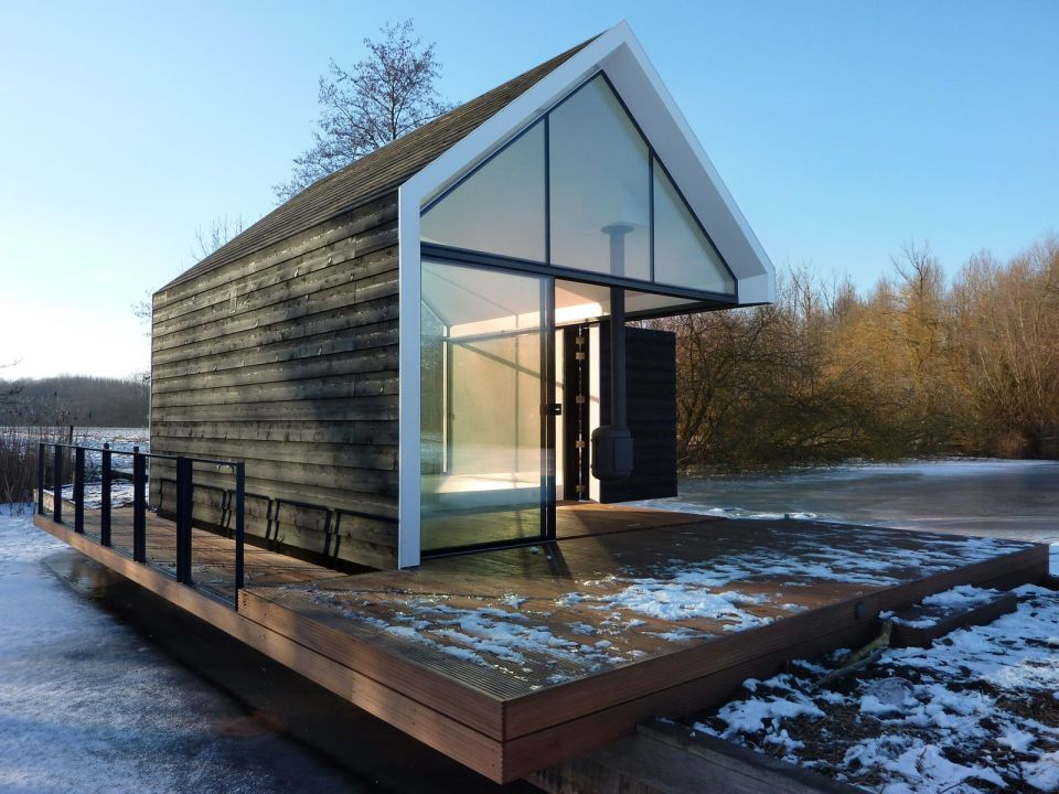 This tiny 226 sq ft lake house opens to the outdoors with a folding wall. 2by4-architects has also designed a prefab version. | www.facebook.com/SmallHouseBliss