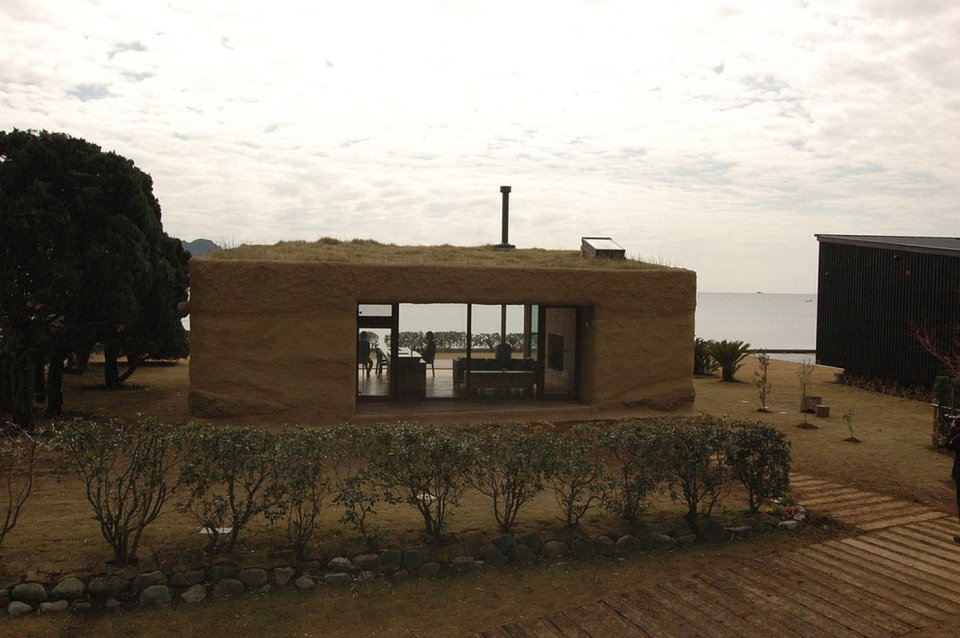 """This """"one room"""" weekend house has sleeping alcoves off the open living area, a green roof and earth-plastered walls. 