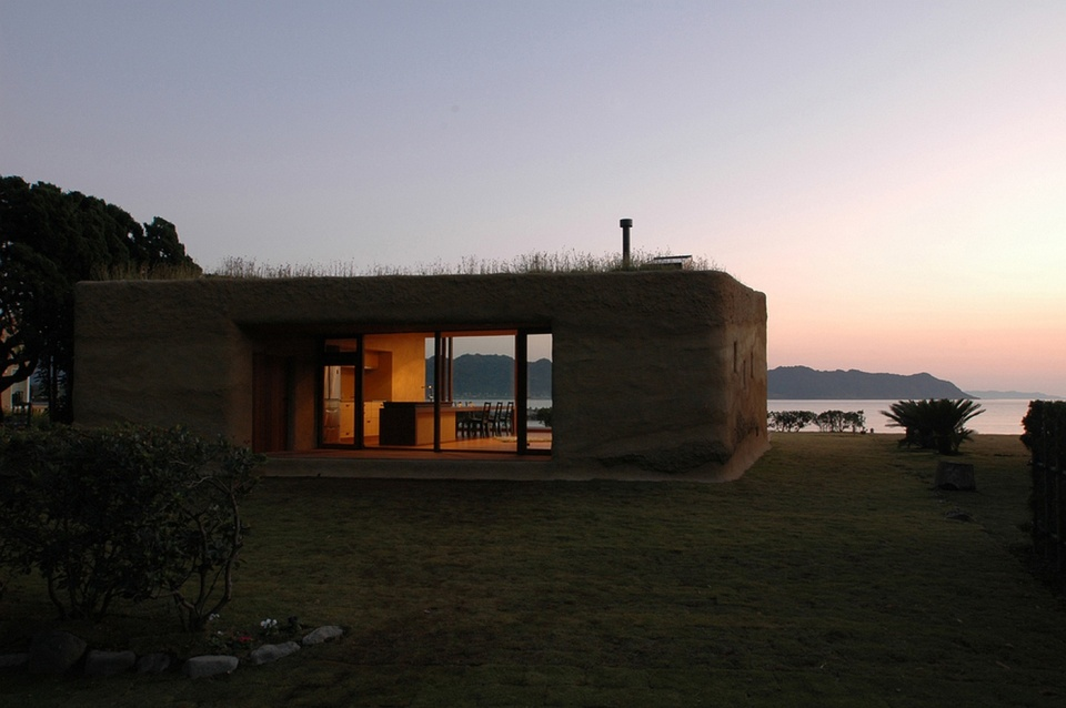 "This ""one room"" weekend house has sleeping alcoves off the open living area, a green roof and earth-plastered walls. 