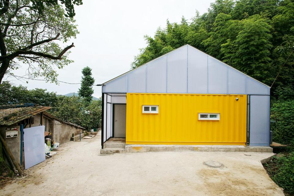 This low-cost shipping container house is covered by a tent-like polycarbonate structure to create semi-outdoor spaces between and around the containers. | www.facebook.com/SmallHouseBliss