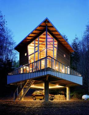 This elevated cabin features a double-height corner window. It has 800 sq ft and a pair of lofts for sleeping. | www.facebook.com/SmallHouseBliss