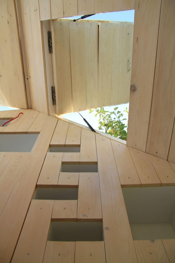 "The ""Spirit Shelter"", a tiny structure designed for self-reflection, has lofted bed and study spaces that cantilever over the main floor. 