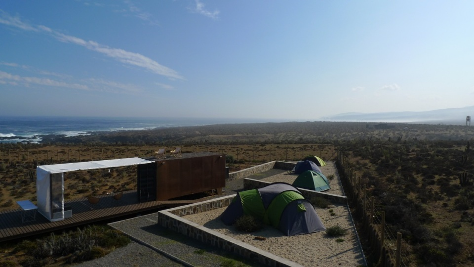 Located near a beach in Chile, this camping compound has a shipping container kitchen/bath, water tower and tent pads. | www.facebook.com/SmallHouseBliss