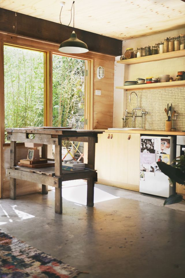 A detached two-car garage was transformed into this bright and roomy backyard cottage with a studio floor plan. | www.facebook.com/SmallHouseBliss