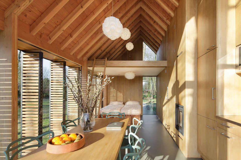 This tiny vacation cottage opens to the garden with a wall of shutters. Built-in cabinetry houses the bathroom, fireplace and kitchen. | www.facebook.com/SmallHouseBliss