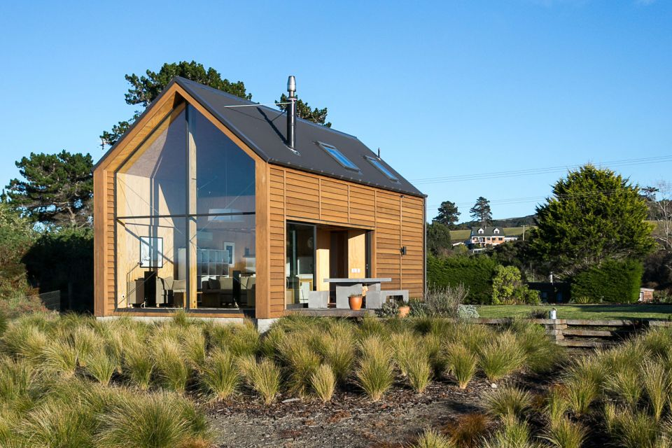 "This New Zealand ""bach"" (a simple vacation home) has a 592 sq ft main level plus two attic loft bedrooms. 