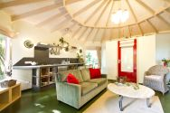 """Forest House"" is a yurt-like tiny cottage with rafters radiating out from the center and an open studio floor plan. 