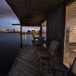 A ramshackle exterior conceals a modern one-bedroom home in this dock house perched over a river within sight of downtown Tampa, Florida. | www.facebook.com/SmallHouseBliss