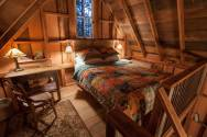 Owl Tree Cabin, a tiny cabin that feels like a treehouse. It has a compact kitchen and bathroom on the 225 sq ft main level plus a loft bedroom.   www.facebook.com/SmallHouseBliss