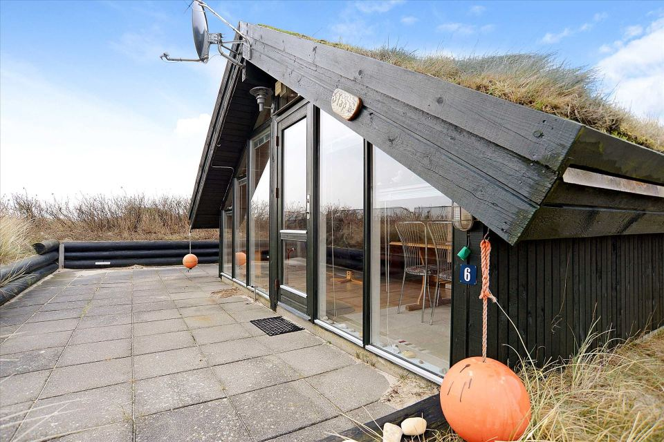 This tiny sod-roofed house sits among the sand dunes in northern Denmark. It has one bedroom in 430 sq ft. | www.facebook.com/SmallHouseBliss