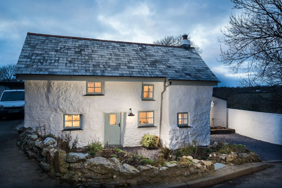"""Sweetpea Cottage, a 300-year-old plastered stone cottage in Cornwall. The two-bedroom cottage was built in 1680 and recently updated in a """"vintage country glamour"""" style to brighten the interior. 