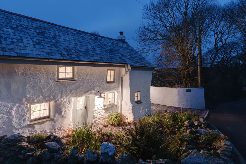 "Sweetpea Cottage, a 300-year-old plastered stone cottage in Cornwall. The two-bedroom cottage was built in 1680 and recently updated in a ""vintage country glamour"" style to brighten the interior. 