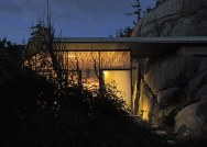 Half-hidden by dense vegetation, this modern cabin is tucked into a rocky Norwegian coastline. It is a 323 sq ft studio design with a sleeping loft suspended from the ceiling. | www.facebook.com/SmallHouseBliss